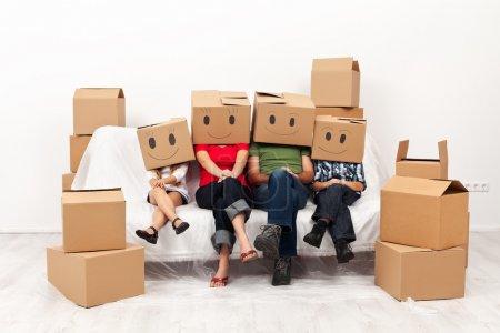 Photo pour Une famille heureuse dans leur nouvelle maison s'amuser ensemble, assis sur le canapé - image libre de droit