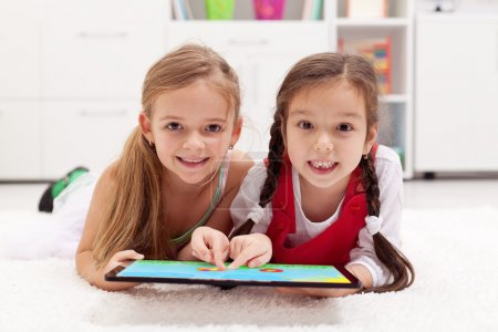 Little girls using tablet computer as artboard
