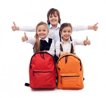 Foto de Regreso a la escuela el concepto con feliz niños dando pulgares arriba muestra - aislado - Imagen libre de derechos