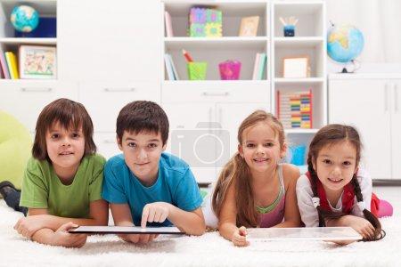 Photo pour Enfants heureux à l'aide d'ordinateurs tablette - image libre de droit