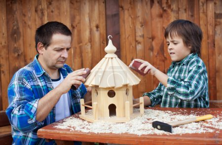 Father and son working on bird house together