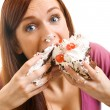 Cheerful woman eating pie, isolated over white bac...