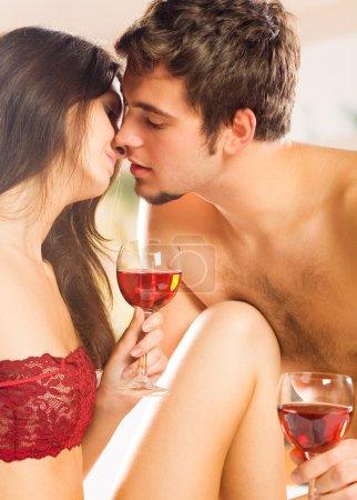 Photo pour Jeune couple heureux célébrant avec du vin rouge dans la chambre - image libre de droit