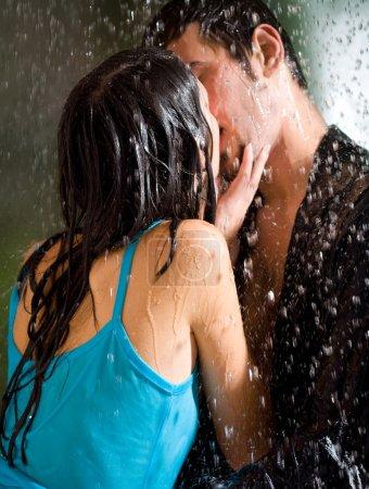Photo pour Jeune couple amoureux heureux étreindre et embrasser sous une pluie battante, à l'extérieur - image libre de droit