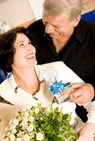 Cheerful senior couple with gifts indoor