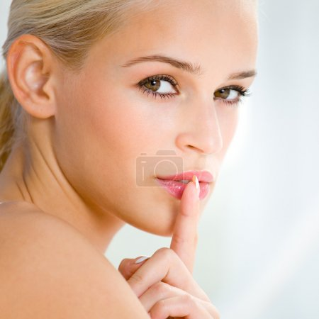 Photo for Portrait of beautiful blond woman with finger on lips - Royalty Free Image