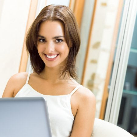 Photo for Cheerfull smiling woman working with laptop, at home - Royalty Free Image