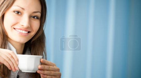 Cheerful smiling business woman with coffee