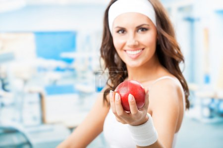 Photo for Cheerful woman with red apple, at fitness center or gym, selective focus on hand. - Royalty Free Image
