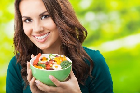 Photo for Portrait of happy smiling young woman with vegetarian vegetable salad, outdoors - Royalty Free Image