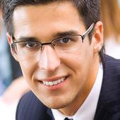 Portrét šťastný usmívající se podnikatel v kanceláři