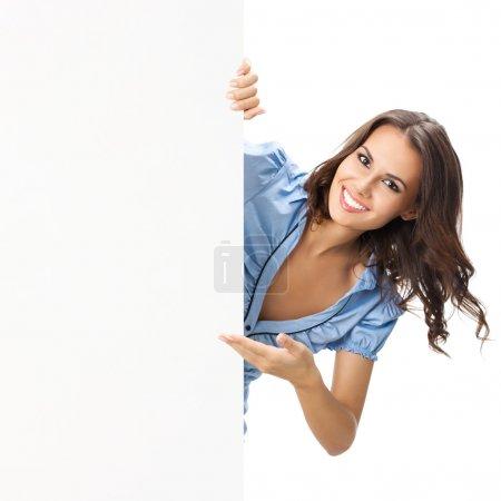 Photo pour Heureuse souriante belle jeune femme montrant le panneau blanc ou fond, isolé sur fond blanc - image libre de droit