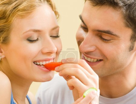 Cheerful young couple eating together tomatoes...