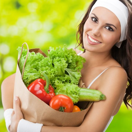 Photo for Portrait of happy smiling young beautiful woman in fitness wear holding grocery shopping bag with healthy vegetarian food, outdoors - Royalty Free Image
