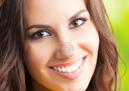 Photo pour Portrait de la belle jeune heureuse femme souriante, à l'extérieur - image libre de droit