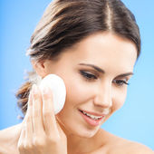 Mladá žena čištění kůže vatový tampon, nad modrá