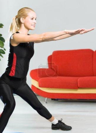 Photo pour Jeune femme en vêtements de sport, faire de l'exercice de remise en forme, à l'intérieur - image libre de droit
