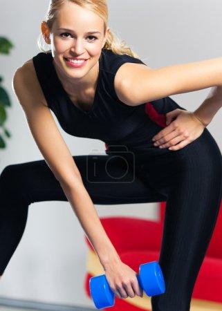 Photo pour Jeune femme souriante heureuse en vêtements de sport, faire de l'exercice de fitness avec haltères, à l'intérieur - image libre de droit