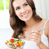 Woman eating salad, indoors