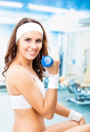 Photo pour Femme gaie en tenue de fitness faisant de l'exercice avec haltère, au centre de fitness ou au gymnase - image libre de droit