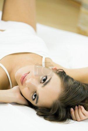 Photo pour Jeune belle femme souriante heureuse réveiller sur lit - image libre de droit