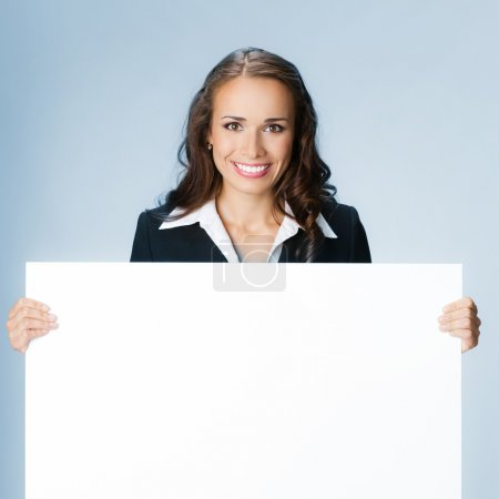 Photo for Happy smiling young business woman showing blank signboard, over blue background - Royalty Free Image