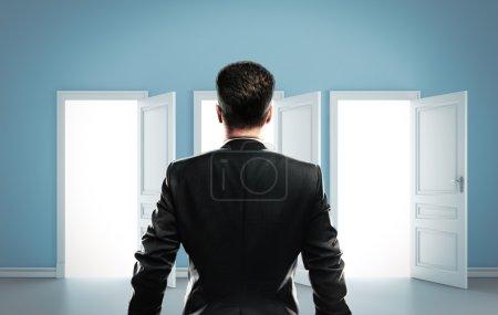 Photo pour L'homme choisit parmi trois portes - image libre de droit
