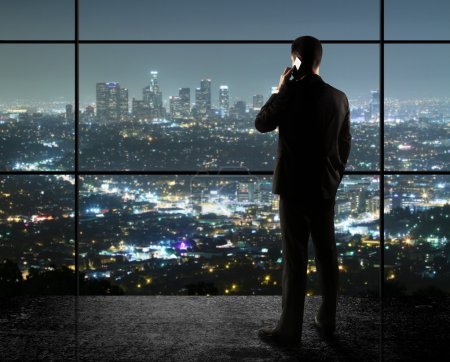 Photo for Businessman with phone looks in night city - Royalty Free Image