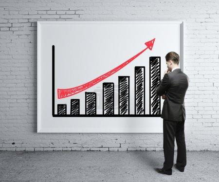 Photo pour Homme d'affaires en regardant la courbe de croissance sur le Bureau - image libre de droit