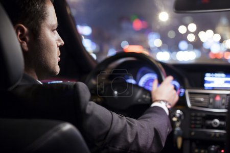 Photo for Businessman driving a car at night - Royalty Free Image
