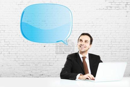 Photo pour Homme d'affaires assis avec ordinateur portable et bubbletalk bleu - image libre de droit