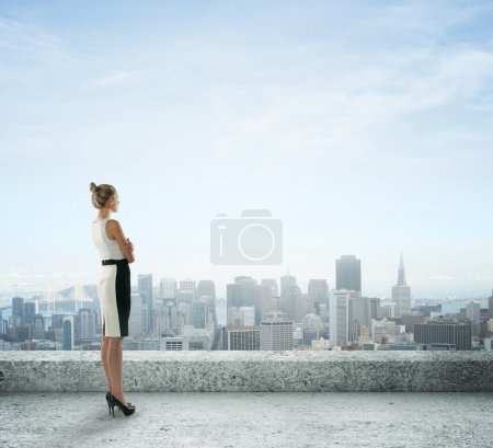 Businesswoman on roof looking at city...