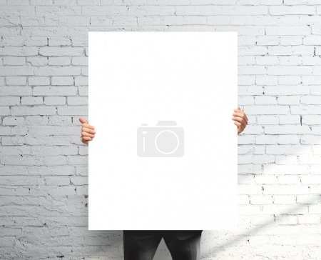 Photo for Businessman holding white blank poster - Royalty Free Image