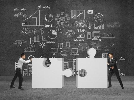 Photo pour Deux hommes d'affaires met puzzle sur la salle de béton - image libre de droit