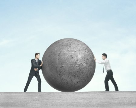 Photo for Two businessman pushing concret ball - Royalty Free Image