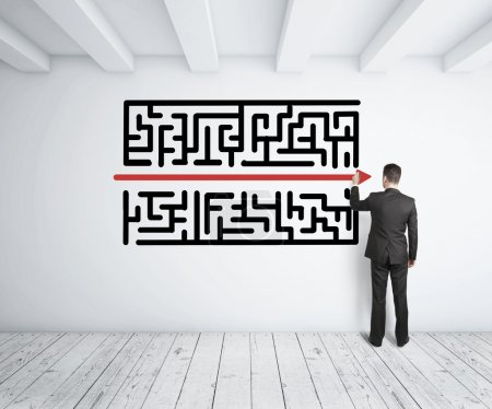 Photo for Businessman drawing maze on white wall - Royalty Free Image