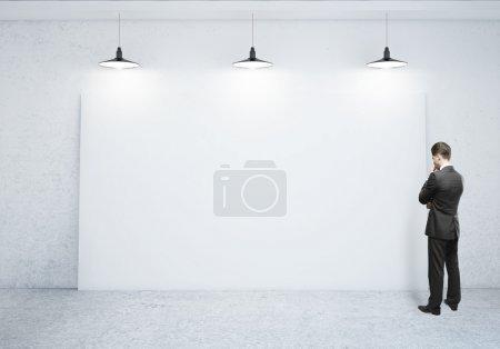 Photo pour Homme d'affaires en regardant affiche vide - image libre de droit