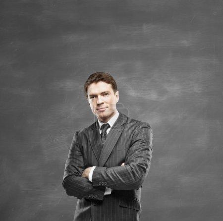 Photo pour Homme d'affaires, debout sur un fond de tableau noir - image libre de droit