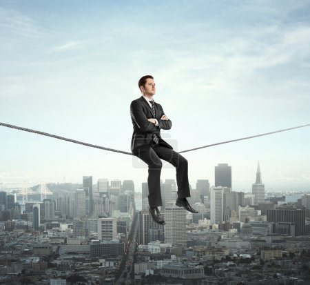 Photo for Businessman sitting on rope and city - Royalty Free Image