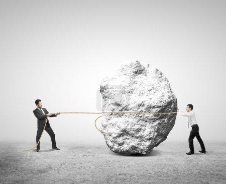 Photo pour Deux hommes d'affaires tirant un rocher de corde - image libre de droit