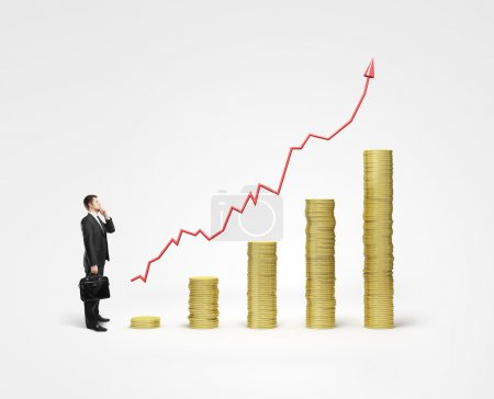 Photo for Businessman looking on gold coins chart - Royalty Free Image