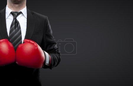 Photo pour Homme en gants de boxe isolé sur fond noir - image libre de droit