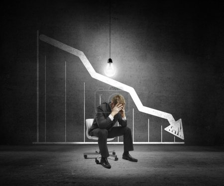 Photo for Sad businessman sitting on chair and drawing chart on wall - Royalty Free Image