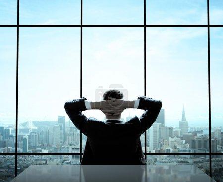 Photo pour Homme d'affaires détendu assis au bureau - image libre de droit