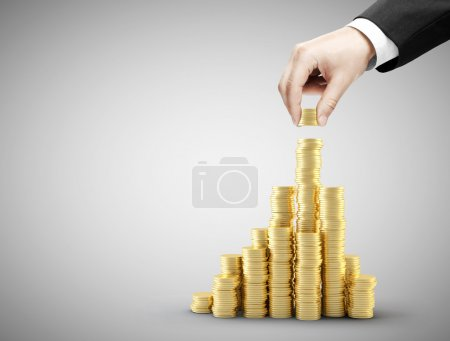 Photo for Hand holding coins and build coin chart - Royalty Free Image