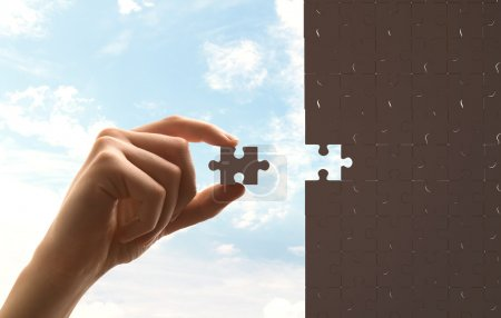 Photo for Businessman built of puzzle on sky background - Royalty Free Image