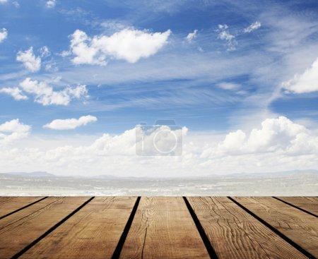 Photo pour Plancher en bois et ciel bleu avec nuages - image libre de droit