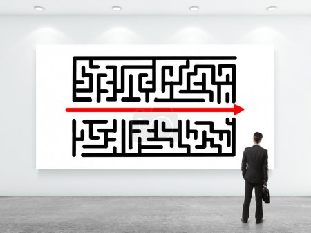 Photo for Businessman looking at labyrinth on white poster on wall - Royalty Free Image