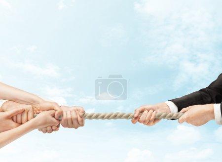Photo pour Mains sur iverses remorqueur de guerre sur fond de ciel - image libre de droit