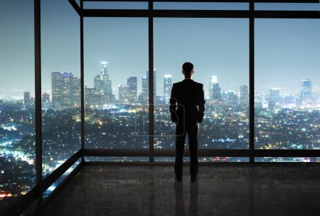 Photo for Businessman standing in night office - Royalty Free Image